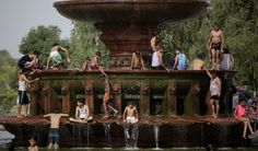 People cooling off at a large fountain near the India Gate monument in New Delhi, India. Kids & adults. Summer heat wave. Lion's head. NY Times