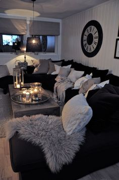Black couch with pillows... Id love to make the grey pillows and blankets RED. and where the circle piece on the wall is, put the elvis/Marilyn/james dean picture!