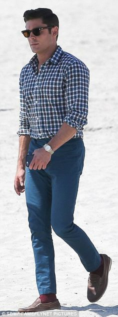 Dapper dude: Zac was unusually covered up for the beach in blue trousers and a checked shirt