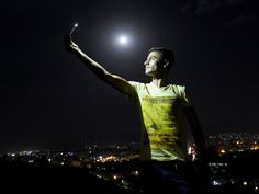 "An Afghan man is illuminated by the light from his phone while taking a selfie in Kabul, as a view of the ""supermoon"" is seen in the background.  Wakil Kohsar, AFP/Getty Images"
