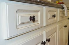 Painted Kitchen Cabinets - blogger used Sherwin Williams Cashmere (Antique White color)and foam roller and he finish looks incredibly smooth! she swears it looks sprayed. Valspar Glaze in Raw Umber color