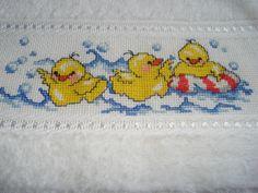 Toalha infantil, bordada em ponto cruz, com motivos de patinhos. Medida 20x40 cm.