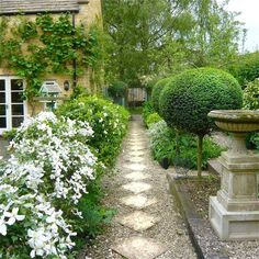 A formal garden with stone and gravel walkway, flowering shrub border and Europe. - A formal garden with stone and gravel walkway, flowering shrub border and European style cast stone - Gravel Walkway, Gravel Garden, Garden Paths, Walkway Garden, Stone Walkway, Stone Paths, White Gardens, Small Gardens, Formal Gardens