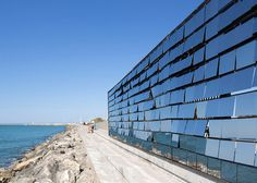 Over 300 mirrored flaps are lifted up and down by the breeze to animate the facade of this seaside structure.