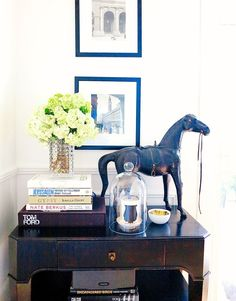 Styled console table with books, statue, framed pictures, and flowers