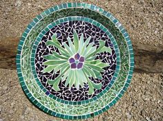 Mosaic Glass and Tile Bird Bath - This Garden mosaic bird bath is a green and purple cut glass flower which has been centered with a beautiful crystal.  The bird bath and the flower are both outlined with beautiful green glass tiles.  The bath measures 16.5 inches in diameter.