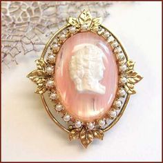 From the 1960s, this pin is a gorgeous cameo creation made of French pink and white ribbon glass in a frame of lustrous white seed pearls.