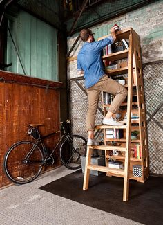 An tall bookshelf features an ingenious built-in ladder.