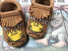 And they made him King of all the Wild Things. Crowns and crossing arrows inspired by the beloved book, these custom, handpainted, one-of-a-kind, Wild One baby moccasins make the sweetest, keepsake. Hand-painted by me - Minnetonka leather moccasins size 0 infant through 6. Also listed in my shop, is a bootie style with a black flap velcro closure.  Free Range Mama is a free-hand, completely custom, hand-painted collection of keepsake baby booties and moccasins! My personalized shoes make the…