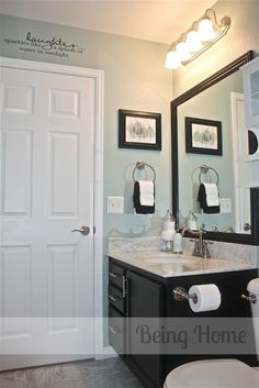 Bathroom completely repainted in Rainwater, by Martha Stewart paint. All trim was painted in ultra white, by BEHR paint. Due to the sturdiness and good condition of the oak vanity, the vanity received two coats of black paint and satin nickel hardware (Liberty Hardware, Chatsworth pull). The mirror was framed with MDF trim and painted black.