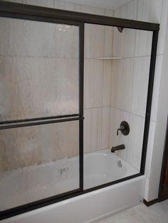 New 12x24 porcelain tiles installed vertically on the shower walls with a custom Oil Rubbed Bronze shower door and Moen fixtures. #bathroomremodel