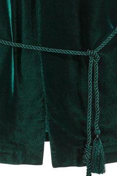 Chaqueta de terciopelo con mangas largas y acampanadas. Cordón torcido para atar en la cintura y sin botones. Forrada.