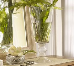 A clear vase with simple greens.