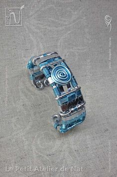 Bijoux fantaisie : Bracelet « Indiana » dit « Eau qui danse » v1 - Réalisation [ Fait-Main ] avec des fils métal en Aluminium (Ø0,8/Ø2 rond et 3,5/5 plat). Sur les tons de Bleu (Bleu Turquoise, Bleu Glacé) et d'Argent, ce bracelet retrace le chemin de l'eau. « Eau qui danse », voilà son vrai nom. Regardez les ondes, les flux, la symbolique d'un chemin, la vie de cette eau qui coule au gré des vents... Avec un collier attrape-rêves autour de votre cou ou dans votre maison... Des idées…