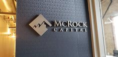 """Custom cut brushed aluminium logo for """"McRock Capital"""" specializes in growth capital and later stage investing in intelligent infrastructure companies. Sign Design, Toronto, Investing, Stage, 3d, Signs, Logo, Interior Design, Nest Design"""