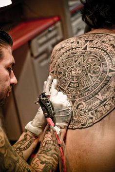 Tattoo artist inking Mayan calendar tattoo.