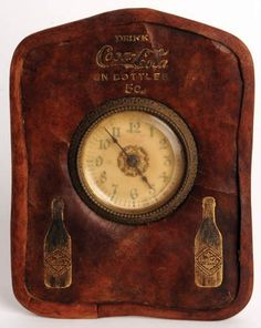 "EARLY 1900'S COCA-COLA LEATHER DESK CLOCK  Early 1900's leather desk clock gold stamped with two bottles ""In Bottles"". Some cracking. Leather edge has been recreated to reinforce edges. Wear on gold stamping"