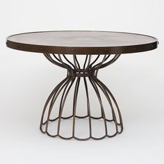 Subtle gray-toned, pie-shaped marquetry forms the top of the Florentine Round Dining Table. A final matte topcoat gives it protection and added durability. The table top's metal rim and base are iron with an antique bronze finish. candelabra, studio A