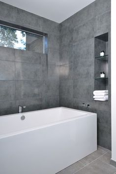 Keep it clean and simple with large-format gray tiles and a gorgeous big white bathtub. This cool and contemporary bathroom has a minimalist spa vibe that I find appealing and tranquil.