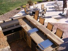 This outdoor kitchen is constructed of all natural stone and features a built-in grill, smoker and other appliances including a deep fryer. It also serves as an eat-at counter for the patio, fire-pit and pool areas.