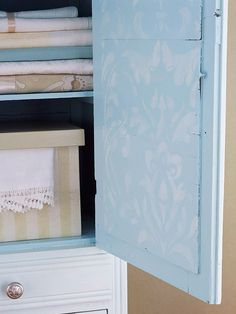 Revamped Armoires for Small-Space Storage  Easy Vintage Stencil: Use a stencil to create this damask design on the inside panel of the door. Applying a thin layer of paint gives the pattern a not-so-perfect, vintage feel.