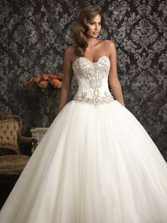 Style: 9017 -  An exquisite ballgown in satin and English Net. The strapless bodice features a sweetheart neckline, delicate boning, and Swarovski crystals. The ball gown skirt is gathered with a chapel train. Colors: White/Silver, Diamond White/Silver. Fabric: Satin, Organza, English Net. Sizes: 2 - 32 . from Allure Bridals.