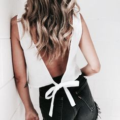 Open back white top with bow in the back. Simple in the front with detail in the back. Perfect top for any summer outfit. Paired with black high waisted, ripped / frayed jean shorts. I love her beach waves and hair color too.