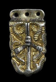 Carolingian Silver-Gilt Foliate Strap End    8th-9th century AD . A cast tongue-shaped strapend with flat pierced attachment plate, central bar and surround of fleshy leaves.