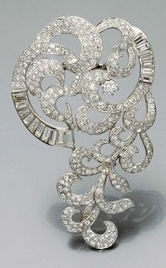 A magnificent platinum, white gold and diamond brooch, circa 1935. Designed as stylised scrolls and feathers set with pavé diamonds.