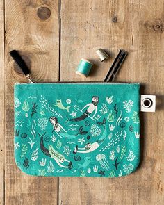 Sea Spell Large Zipper Pouch - A large zipper pouch made from sturdy 100% cotton is perfect for storing drawing supplies, small accessories, travel essentials and more. A metallic zipper keeps contents secure, while a grommet tab adds convenience. Enchanting merfolk swim in a swirl of aquatic greens and blues amongst playful mercats and merdogs. Merfolk, Travel Essentials, Zipper Pouch, Travel Style, Travel Bags, Cosmetic Bag, Blues, Contents, Sea