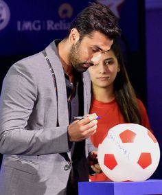 Ranbir Kapoor signing on the ball at the launch of Indian Super League