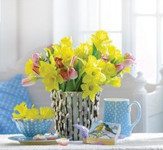 Yellow daffodils and pink tulips in a pussy willow vase. Soft blue with white polka dots decor. Great for spring!