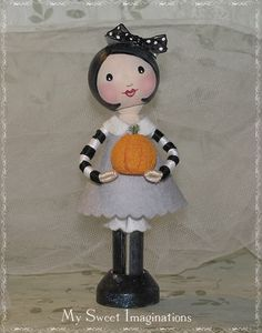 Thought it would be fun to make a black and white doll. Since I had no gray fabric, tried out some woolfelt for her dress, collar, and bloomers. Made her a little pumpkin to hold for Halloween, although I didn't intend for her to be a Halloween doll. I think she turned out pretty cute!