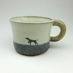 An earthy mug with grey and white glaze and hand painted dog print.  It was thrown in my studio in rural Inverness with red clay then