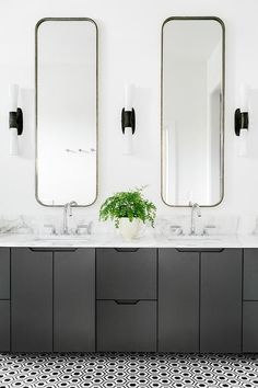 Two tall curved mirrors proudly mounted over a modern black dual waistband topped with a white marble countertop and dual sinks. Black and white hex tiles add charming character to this bathroom space lit by black and white 2 light bath sconces.