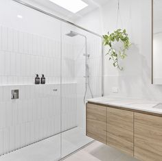 Mark Sansone Perth Building - WA builder Mark used Smartstone Calacatta Manhattan as benchtop on the vanity in this white bathroom, giving it a natural accent and complementing the sky-lit and beautifully tiled shower area. #smartstone #Bathroom #renovation #Bathroomideas #Bathroomdesign #renovationideas #renovationBathroom