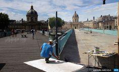 FRANCE, Paris : Spanish artist Alberto Martin Giraldo works on a  trompe-l'oeil painting at the Pont des Arts in Paris on July 18, 2015.  AFP PHOTO / MIGUEL MEDINA