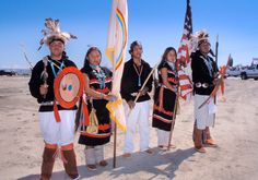 A group of Navajo teens dressed in traditional regalia from the Navajo Prepatory School sophomore class of honor guards carry the Navajo tribal flag and US stars and stripes