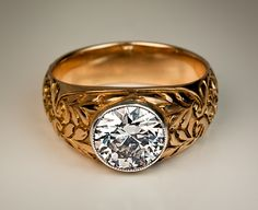 A Vintage Russian Diamond Ring  made in Moscow between 1908 and 1917  A 14K gold ring features a sparkling old European cut diamond set in a silver milgrain bezel.   The diamond is 7.9 x 4.3 mm (approximately 1.70 ct, H-I color, VS2 clarity).  The ring is decorated with finely chased and engraved stylized floral designs.  Marked with 56 zolotnik gold standard and maker's initials.