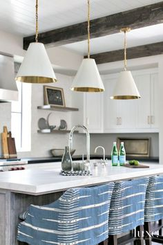 A trio of pendants from Linden Rose & Co. bring a dash of bohemian glamour to the kitchen. Barstools in a Peter Dunham Textiles fabric draw up to an island with a top by Epic Ceramic & Stone. The Rohl faucet is from Pirch.: