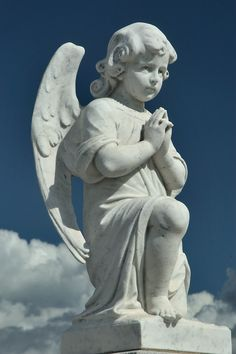 A young angel (cherub) sitting on a cloud in Saint Louis Cemetery No. 3.  asergeev.com