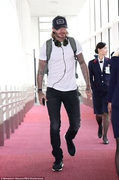 Missing Brooklyn? David Beckham, 42, cut a downcast figure as he touched down in Haneda International airport, Tokyo, Japan on Tuesday in a casual ensemble