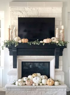 Pretty display of pumpkins in front a classic fireplace.