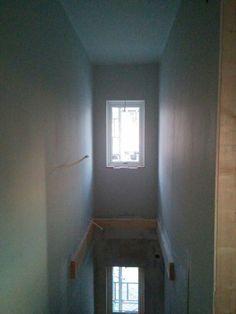 Fönstersmygar kommer på plats och målning pågår i trappen.
