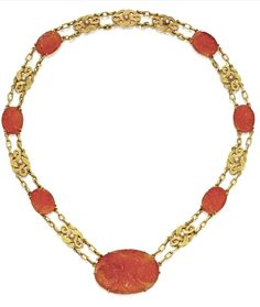 18 karat gold, carved carnelian and seed pearl necklace, Tiffany & Co, circa 1915. Possibly designed by Louis Comfort Tiffany, composed of carved carnelian plaques of floral design, connected by gold links 'en esclavage', set with small seed pearls, length 17 inches, signed Tiffany.