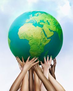 Multiracial hands holding green globe