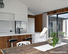 The cedar covers the walls and kitchen cabinetry, finished in Resene Natural stain. The rest of the walls are painted in Resene Black White. picture Jessica Judge