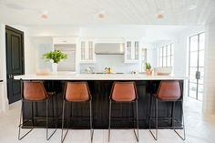 The kitchen was the only room left partially intact during the renovation. Ford painted the existing bottom cabinets black, then brought in modern rustic elements like the Giron leather barstools from ABC Carpet & Home. Rejuvenation's flush mount pendants with copper shades hang above the island | archdigest.com