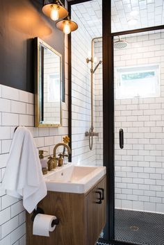 This remodel features Restoration Hardware lights and mirror, a custom vanity and shower doors, along with metal hardware