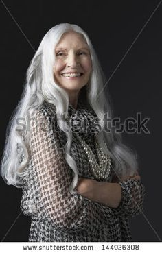 Portrait of a smiling senior woman with long gray hair against black background - stock photo